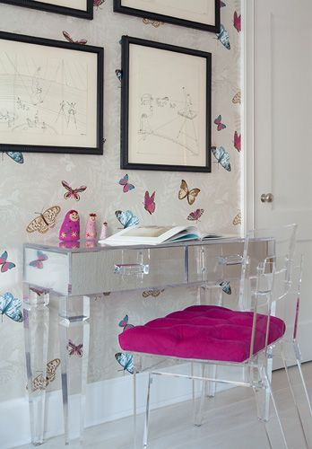source: Fawn Galli Interiors  Mirrored desk, acrylic George II Chair with fuchsia tufted cushion and Farfalla Wallpaper by Nina Campbell.
