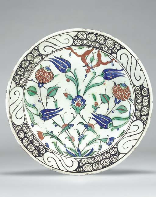 AN IZNIK POTTERY DISH  OTTOMAN TURKEY, CIRCA 1620  With sloping rim on short foot, white interior decorated with a symmetric arrangment of a central tuft issuing two tendrils that join at a single blue palmette, issuing a pair of blue tulips, flanked by a pair of red roses & at the bottom, a red & a blue flower, also from the central tuft, & two more blue tulips, with a red arabesque panel between the two main tulips, the rim with black stylized wave & rock motif...  10¾in. diam.