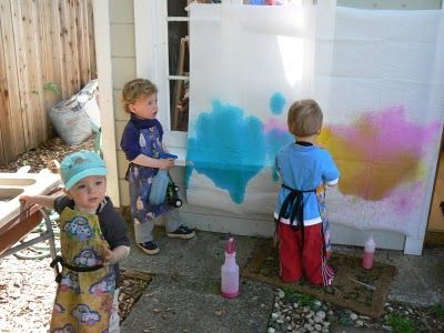 I like the idea of not drawing on a flat surface like on a table, but on a wall instead. I also like it that the children are not using paintbrushes they are using spray bottles and spraying the paint onto the cloth on the wall.