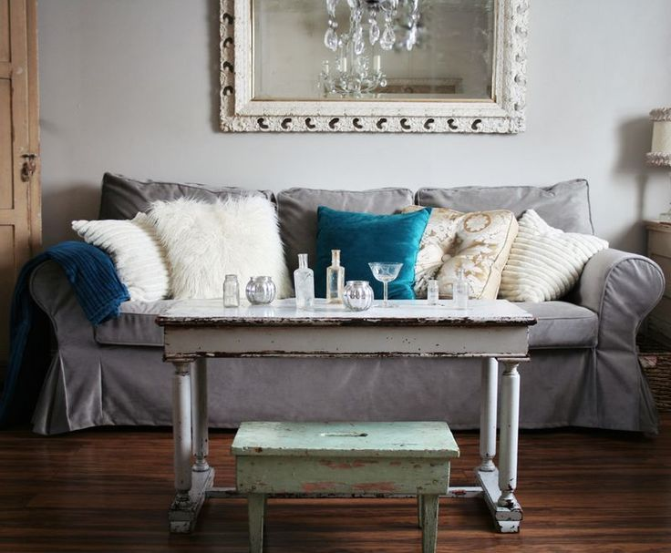 Ikea couch gone chic: grey velvet slip cover and some fun pillows really dress up a living room. Love the pale gray walls gives the room a vintage feel