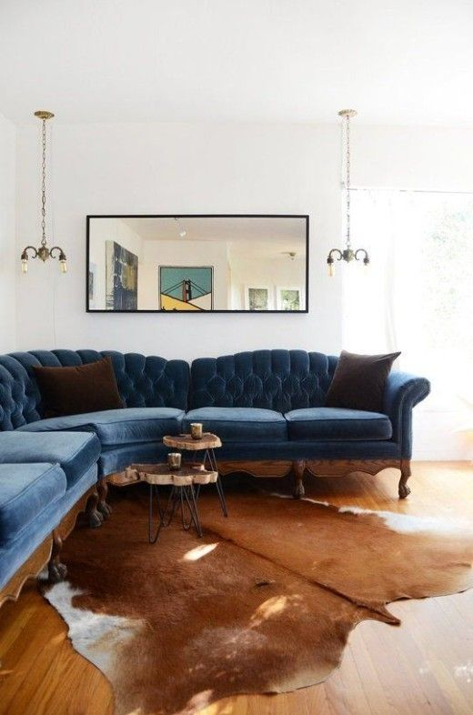 We're swooning over this blue, tufted #velvet sofa and animal skin rug combination.