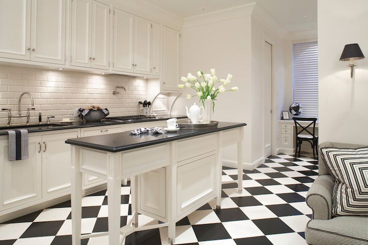 Compact kitchen with white flush front, cabinetry accented with brushed nickel pulls alongside sleek honed black counters with a beveled subway tile backsplash. The kitchen features an undermount single basin sink with bridge gooseneck faucet to the left of a gas stove top with pot filler faucet above. A slim, freestanding island stands centrally within the space atop black and white harlequin tiled floors with a built-in desk at the far end of the room lined with a black French cafe chair.