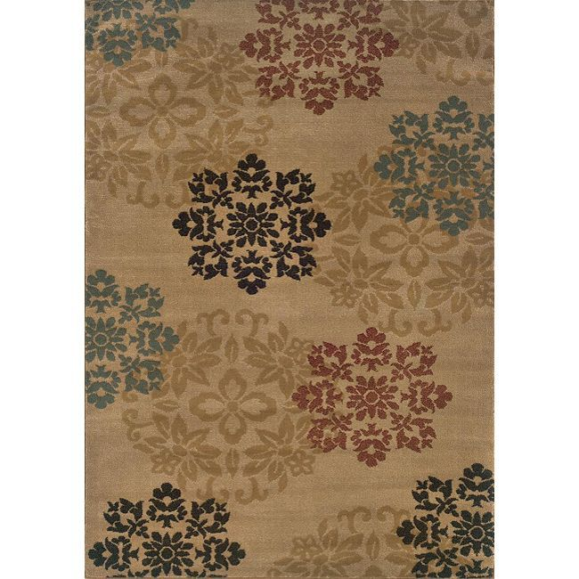 A circular floral pattern styles this machine-woven rug of a durable stain resistant construction in beige, black, green, gold, red and blue. Add texture and style to your home with this allergen-free rug.
