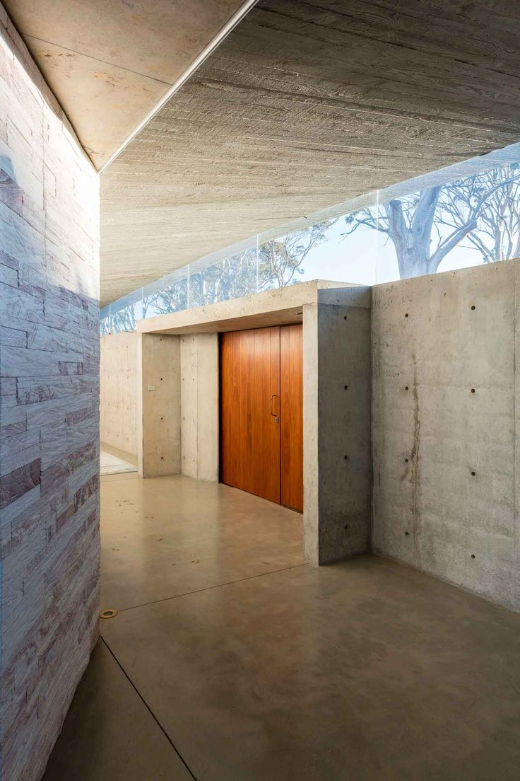 Peter Stutchbury: Invisible House NSW: Clerestory windows without visible structure provide connection to landscape. In situ concrete walls and floor softened by sandstone interior wall cladding.