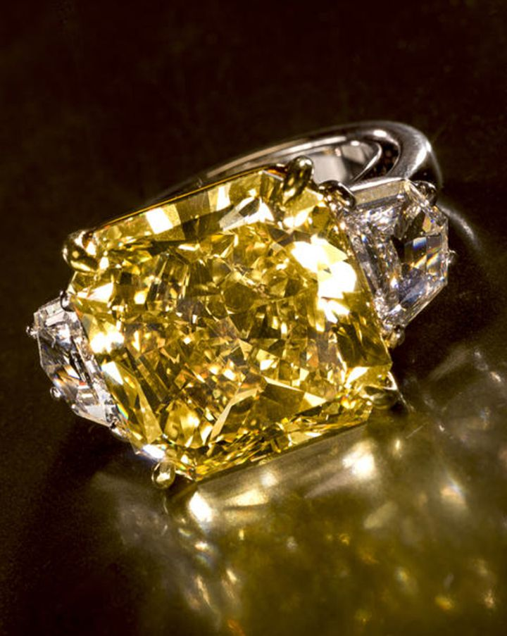 A fancy colored diamond and diamond ring set with a cut-cornered square modified brilliant-cut fancy deep yellow diamond, weighing 16.03 carats, flanked by fancy-cut diamonds; estimated remaining total diamond weight: 2.00 carats; mounted in eighteen karat gold