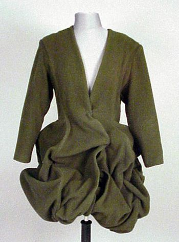 * Sybilla Wired Coatdress Spanish, 1980s Olive green wool, collarless, princess line, single closure at waist, the bottom half wired for individual shaping, pulling up into a poof