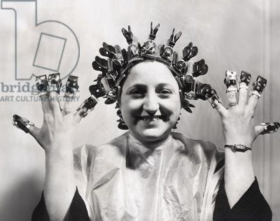 Model wears Helene Curtis remote control permanent wave. March 13, 1940. She wears nail shields invented by David of Wilshire to protect her freshly polished nails. New scientific products were exhibited at the NYC International Beauty Show