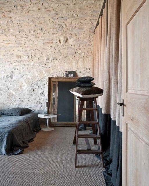 Dark grey and beige bedroom, stone wall, drapery closet, sisal floor