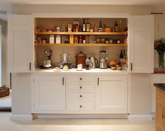 large larder cupboard within the wall with generous bi-fold doors revealing marble and oak shelving. A workstation and ample storage area for food and appliances