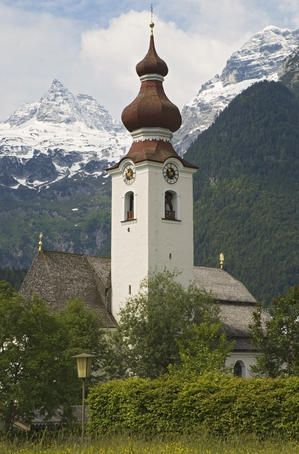 Church tower with snow capped mountains in the background.
