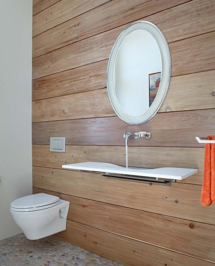 bathroom remodels, spacious toilet with one wall covered in wooden planks, other visible wall is white, round mirror with silver frame, white minimalist modern sink, pebbled floor and plain white toilet seat
