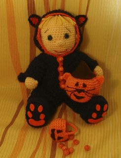 This little adorable guy Tomas is some pumpkins. He has wonderful Halloween cat suite and funny pumpkin the cat.