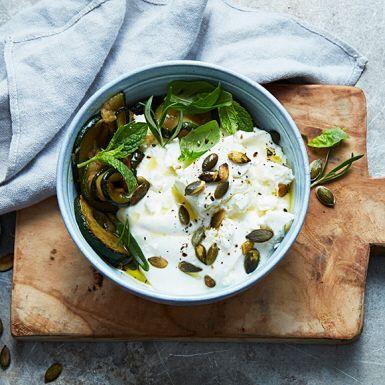 Slopa bär och müsli. Piffa hellre yoghurten åt det salta hållet! Inte alls dumt, och det här är en rätt som du kan variera i all oändlighet. Till den svala, krämiga yoghurten blir det zucchini stekt i vitlök, fetaost, örter och rostade frön. En näve oliver är gott till.
