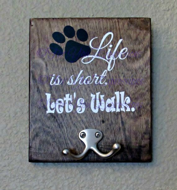 """Life is short, let's walk"". Wooden sign with Dog leash holder. Custom made just for you and your furry exercise partner. Pick your color of vinyl for the words and paw print. Also pick your stain color for the wooden board."