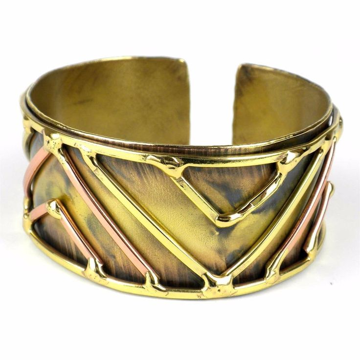 Handmade by South African artisans, this brass cuff is adorned with polished brass and copper geometric accents. The coloration of the brass is achieved by applying high heat rather than paints or dyes. Bracelet dimensions: 27 mm wide x 7 inches long.