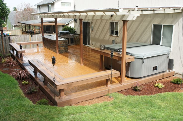 TimberTech Earthwood deck with built in benches, table by the hot tub, built in BBQ and patio cover.