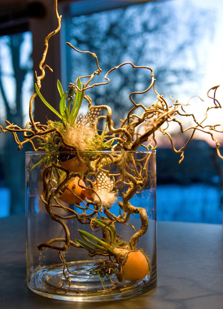 Love the bulbs in egg shells and the touch of feathers. Add a layer of sheet moss at the base to finish it off.