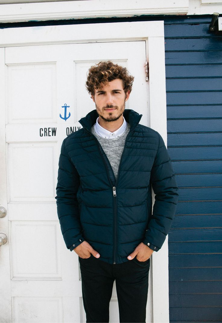 Men's navy puffer jacket, marled gray sweater, white shirt + black trousers.
