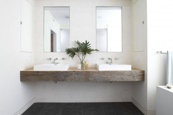Rough-hewn woods have a place in contemporary baths, too. A thick-cut vanity top keeps this bath from feeling too cold. In an otherwise black-and-white space, the wood's natural colorways and grooves create a dramatic accent to the stone floors and textured wall tiles. Topping the piece with minimalist sinks, faucets, and mirrors keep the room steeped in modern style.