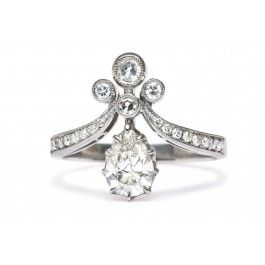 Tiara II Trumpet & Horn's exclusive Tiara ring is reminiscent of Victorian times where jewelry and fashion were inspired by nature and romance. This unique diamond ring is made from platinum and features a 0.71ct EGL certified Pear shape diamond with H color and SI3 clarity. A trio of bezel set single cut diamonds balance this gorgeous prong set center diamond. Further accents of bead set single cut diamonds on the shoulders are enhanced with delicate milgrained edges. Size 7.  $5,700