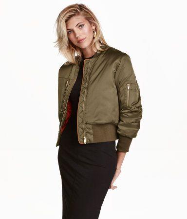Khakigrün. Kurze, wattierte Jacke aus fein glänzendem Webstoff. Modell mit kleinem Stehkragen und Frontreißverschluss. Brust- und Ärmeltasche mit