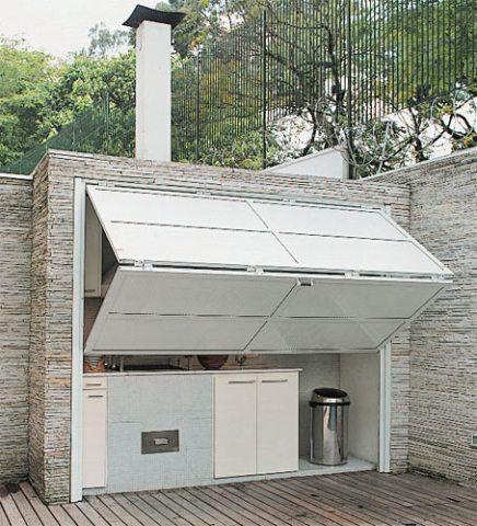 Após o uso, o conjunto fica escondido por uma porta sanfonada manual de alumínio (Serralheria Freire), modelo usado em garagens. Churrasqueira a carvão com grelha elétrica giratória e coifa de inox (da Construflama). Os armários de MDF forrados com laminado melamínico são da Nativa Movelaria e a torneira, da Deca. Na parede, mosaico de vidro Vidrotil.