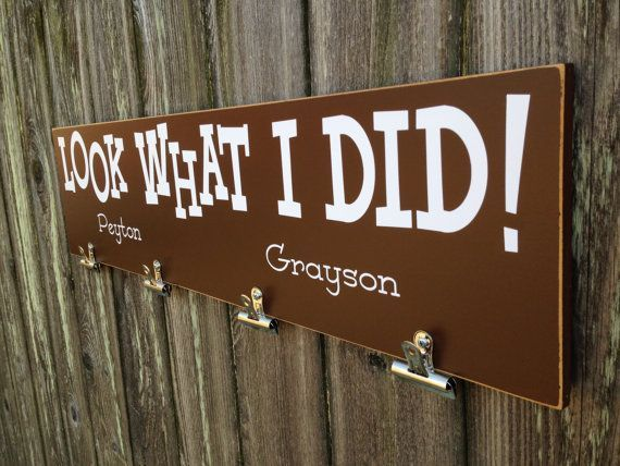 Look What I Did! This is a great way to display your childs art work and they will be so proud to see it hanging up! This is a wood sign made from mdf with a hand painted background, vinyl lettering, metal clips and sealed with a matte finish for protection. It is perfect for your home with a saw tooth hanger on the back, ready to hang!  Dont like the color scheme? Pick your own colors! The last picture shows your vinyl choices and you choose any background color. Please be as specific as…