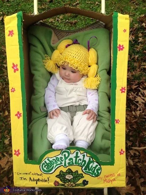 Megan: I cut up a carboard box and handpainted it to resemble a cabbage patch box by looking at a picture of a real one. I crocheted the little wig for...