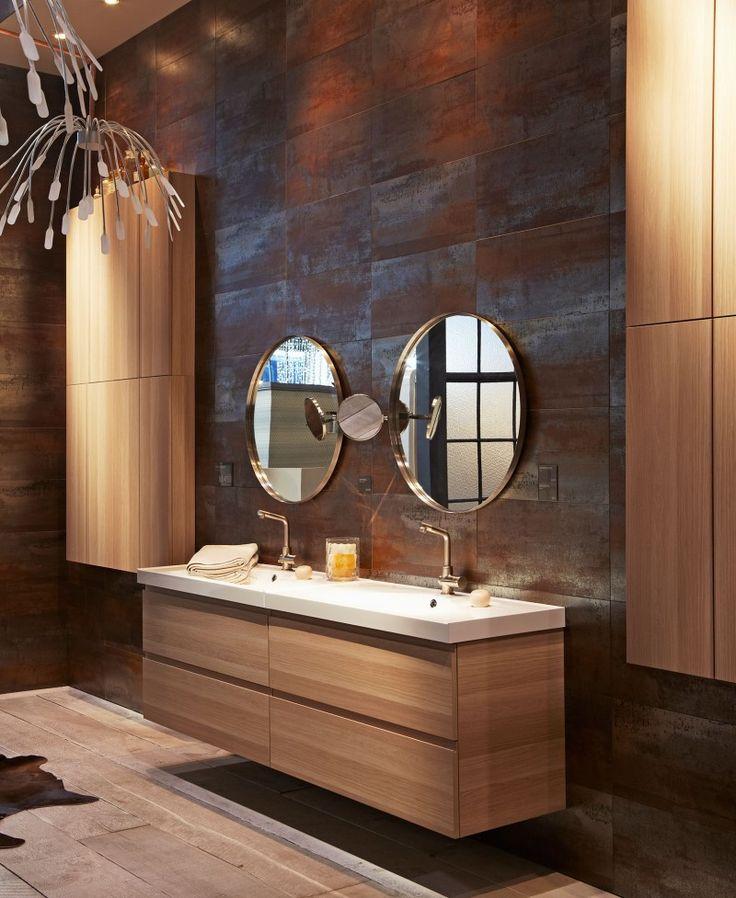 Cette salle de bain IKEA est majestueuse. Avec son parquet naturel, ses meubles en bois, et son haut plafond, la salle de bain est à la fois chic et naturelle. On rêve de s'y prélasser, et de ranger tous nos produits de beauté dans les grands placards situés sous les éviers.