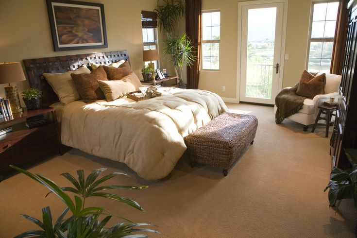 This master bedroom is filled with desert colors, featuring a wicker ottoman, tan comforter, and sand colored carpeting.