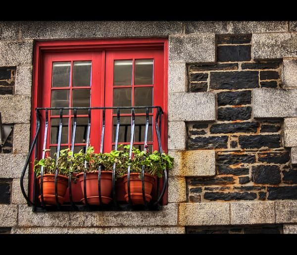 Located on the Halifax waterfront, in Nova Scotia, the old stone wall and wrought iron railings set off the red of the window frame stunningly.