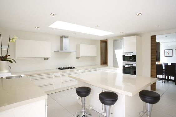 Weech Road - Granit Large open plan kitchen with island. White gloss units with composite stone countertop. Timber highlights throughout the scheme. West Hampstead, North London contemporary rear extension.
