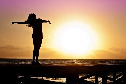 Silhouette of woman standing on pier at sunset