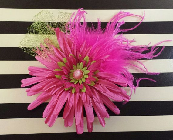 Stand out in a crowd with this vibrant pink and lime flower and feather fascinator. Measures 6 by 6 and is mounted on a 3.5 by 2 plastic haircomb.