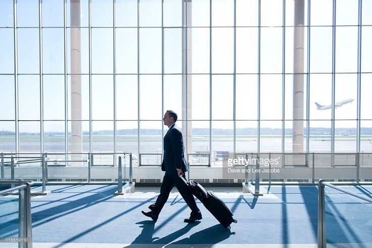 Stock Photo : Caucasian businessman pulling luggage in airport