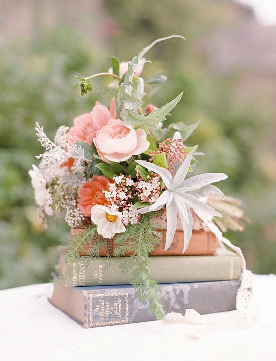 vintage flowers on book wedding centerpiece / http://www.himisspuff.com/rustic-wedding-centerpiece-ideas/20/