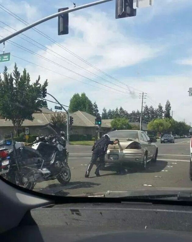 A Modesto police officer pushes a car out of an intersection.