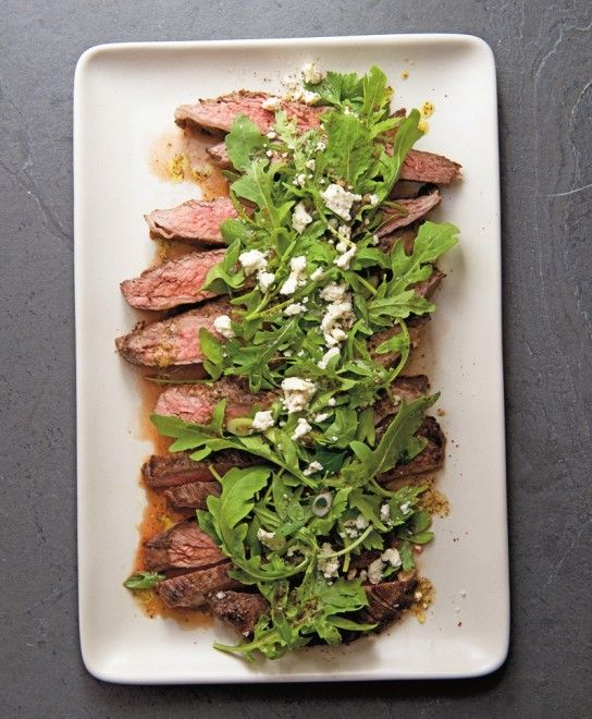 steak with arugula salad in plate elevated view sliced strip steak ...