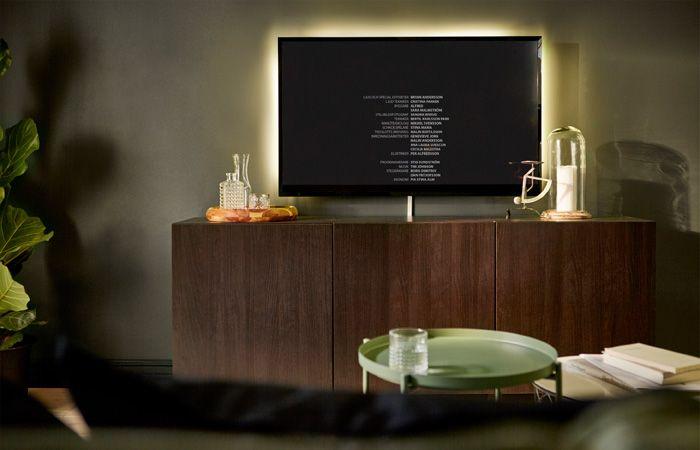 TV colgada en la pared, con una guía de iluminación detrás que evita los contrastes en los espacios oscuros.