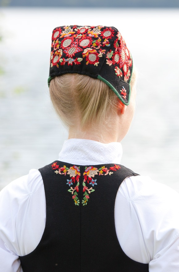 On a Norwegian bunad -- the cap and neck line has fine embroidery that matches in colors.