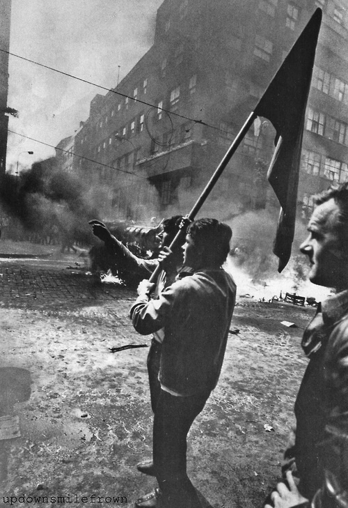 Urged by their government to show no resistance, Czech citizens could show only their flag and fight back with sticks, stones, jeers, and firebombs in a courageous display of defiance against the Soviet invasion, 1968. by Hilmar Pabel