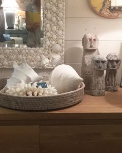 A collection of goodies in the shop. A small glimpse of a huge locally made shell and coral mirror, the work in it is amazing. Below are shells, rattan, stone statues, all on a weathered oak sideboard #Beachwood #furniture #homewares #localart #mirror #avalon #coral #interiors #coastalstyle ⭐️😍🐚