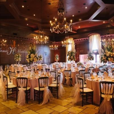 Indoor wedding reception with gold uplighting and tule chair ties  | Brushfire Photography | villasiena.cc