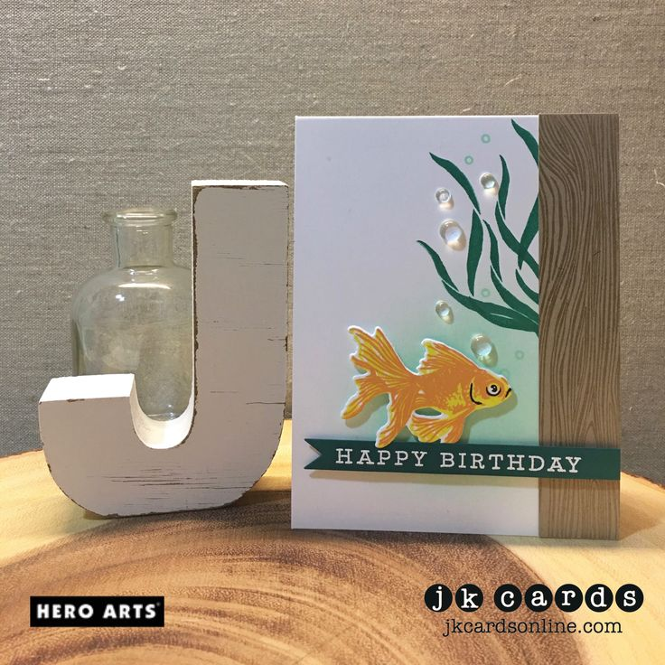 Stamp Sets: Color Layering Goldfish and Many Everyday Messages and Designer Woodgrain Background (Hero Arts); Ink: Lemon Yellow, Orange Soda, Mint Julep, Emerald Green and Black (Hero Arts); Specialty Ink: Versa-Mark; Embossing Powder: Clear and White (Hero Arts); Card Stock: Solar White 110lb and 80lb (Neenah), Kraft and Hunter Green (My Colors); Dies: Color Layering Goldfish Frame Cuts and Little Messages Stamp & Cut (Hero Arts); Embellishments: Clear Droplets (Pretty Pink Po