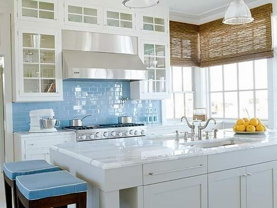 Love this kitchen.  White glass front cabinets with clean lines and modern hardware, Carrera marble counters, and light blue glass tile back splash.