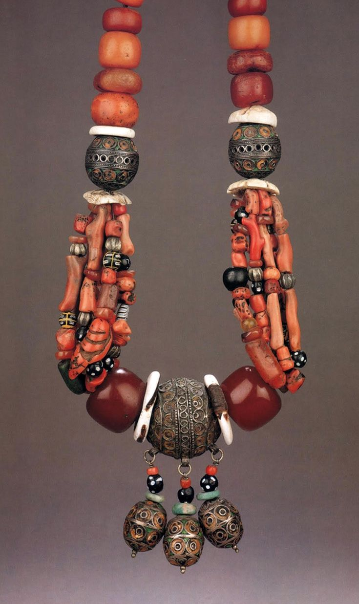Morocco | Detail from a necklace; silver with enamel beads, 'amber' coral, old glass and stone beads, shell