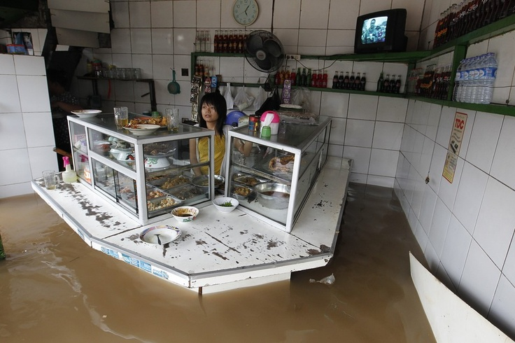 FLOODED FOOD: A woman stood in her flooded food stall in Jakarta, Indonesia, January 17, 2013. Heavy rains triggered severe flooding in large swaths of the capital, leaving at least four people dead and displacing thousands   © Enny Nuraheni   Reuters