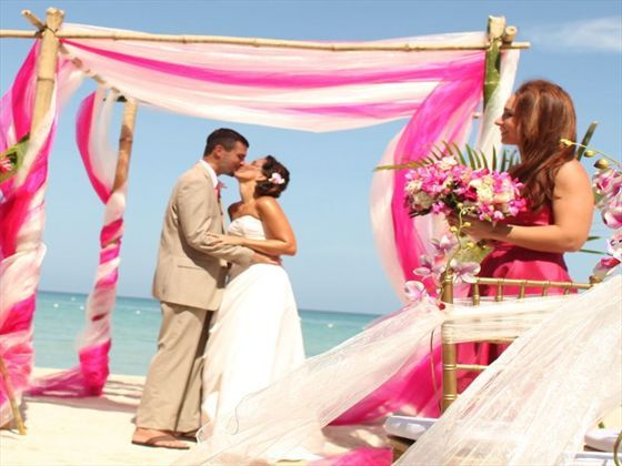 Bride and Groom kiss on the beach at Breezes Bella Costa