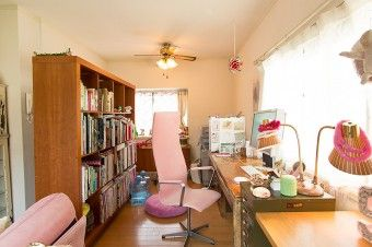 仕事スペースは、リビングを可動式の本棚で仕切った。椅子やソファーはパステルピンクで統一。