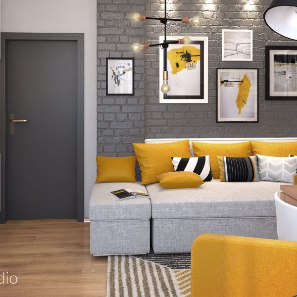 Small living room with dark grey brick walls and grey sofa. Color accents in mustard.